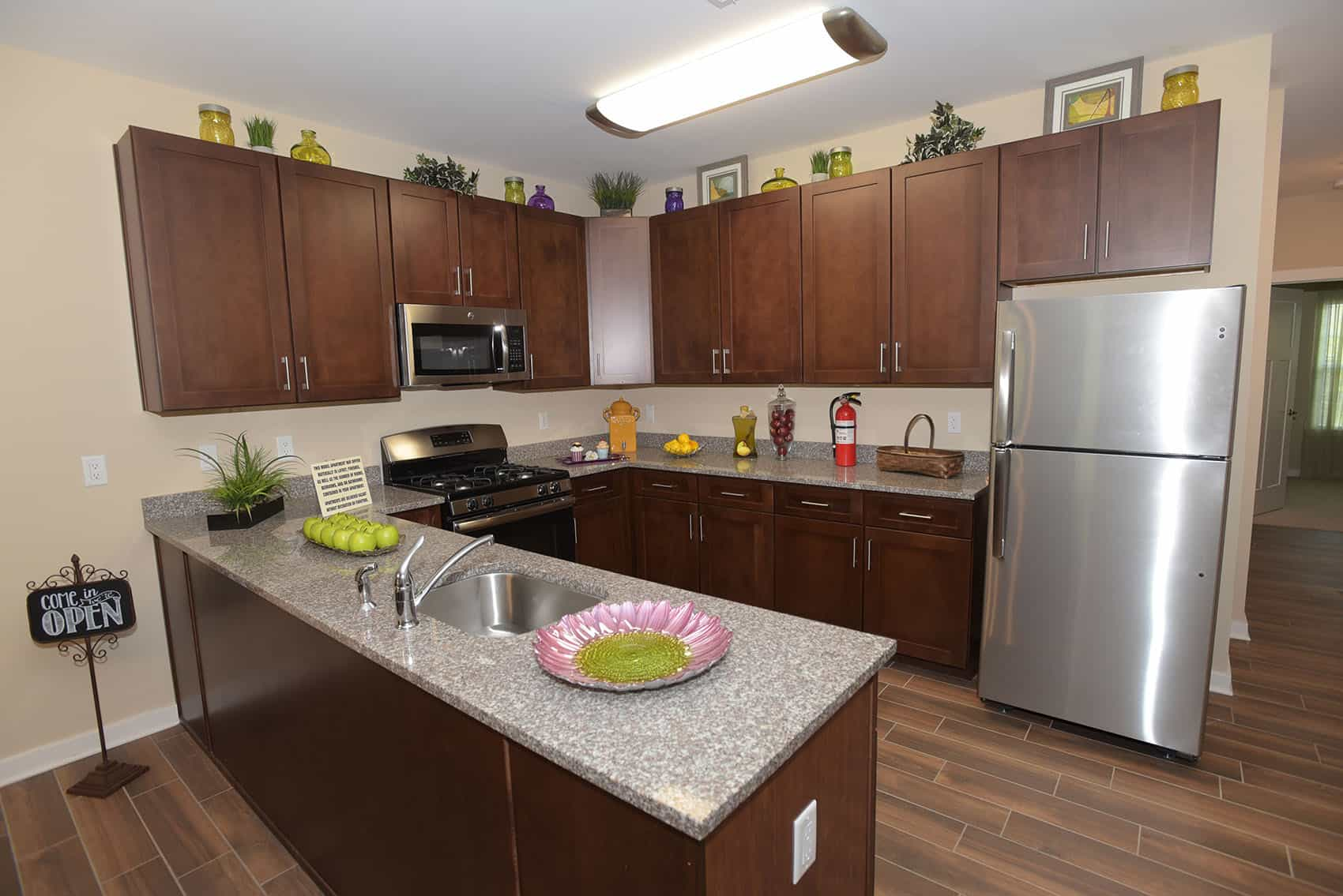 Kitchen with granite countertops and dark wood cabinets in Gardens at Jackson Twenty-One