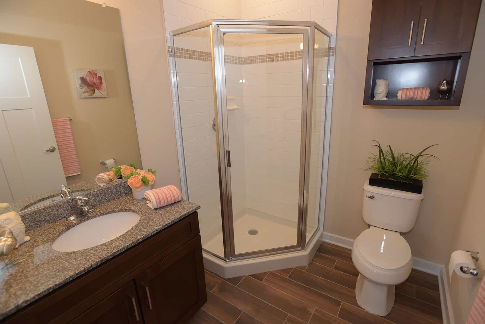 Bathroom with tile flooring and glass enclosed stand up shower with a brown wooden vanity