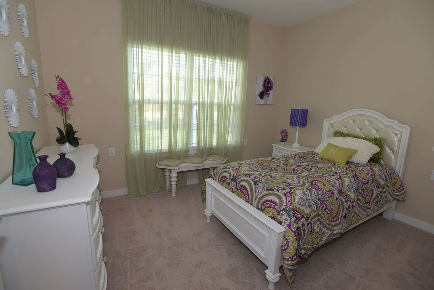 Bedroom at the Gardens at Jackson Twenty-One with carpet flooring and white wooden bed and dresser