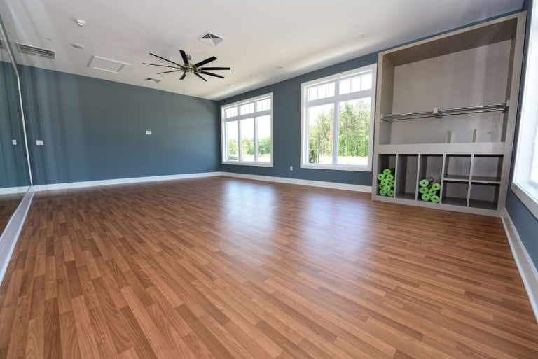 Empty fitness room with wood flooring and yoga mats.