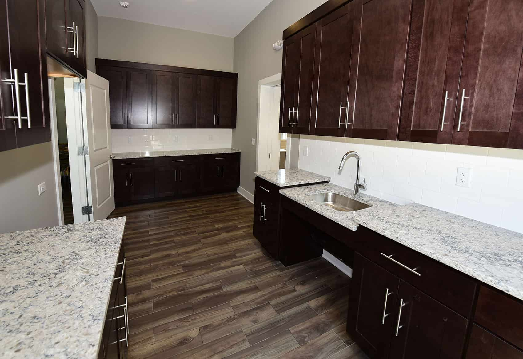 Kitchen area in the clubhouse with brown cabinets and granite countertops