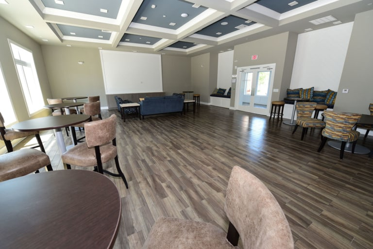 Clubhouse community are with round tables surround by chairs and hardwood floors