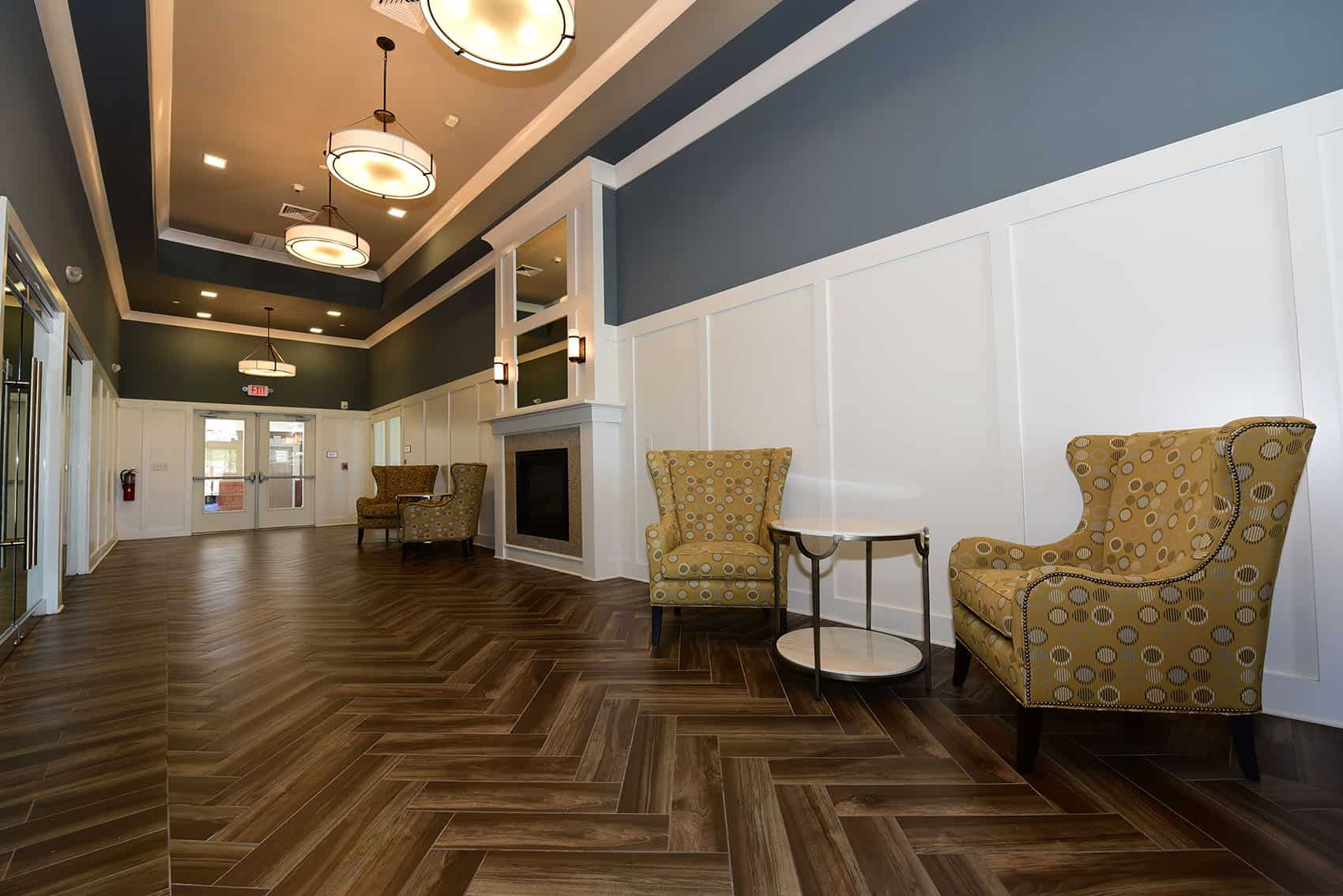 Interior of the clubhouse at the Gardens at Jackson Twenty-One with tiled floors, fireplace, and yellow chairs.