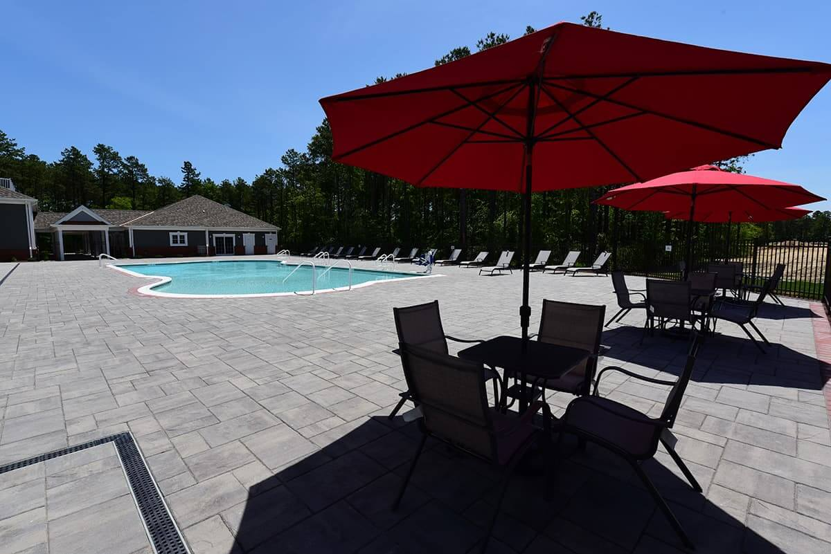 Image of pool, clubhouse, and table with red umbrellas