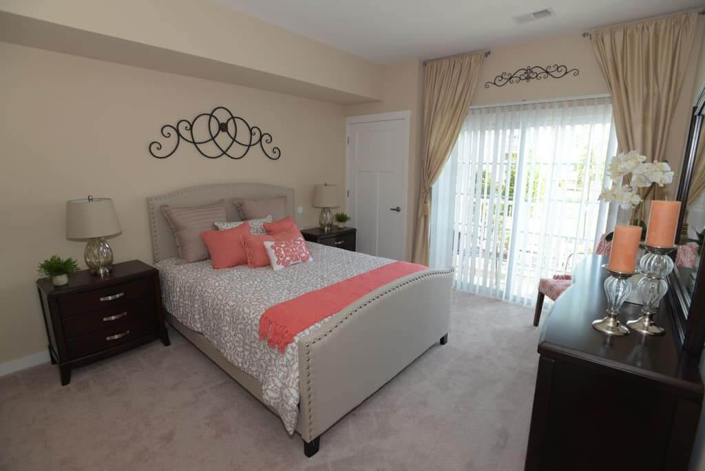 Bedroom with carpet flooring, a queen-sized bed, and two wood nightstands
